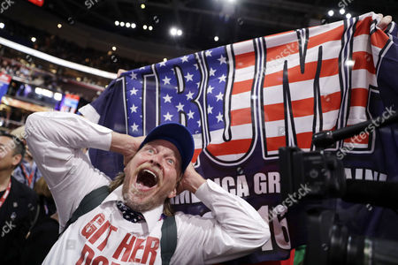 "Stock Picture of Tony Barbieri reacts as the character ""Jake Byrd"" from the ""Jimmy Kimmel Live!"" show as New York delegate Bob Hayssen holds up a Trump flag during the second day session of the Republican National Convention"