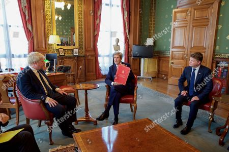 U.S. Secretary of State John Kerry, joined by U.S. Ambassador to the United Kingdom Matthew Barzun, holds up the Foreign Secretary's traditional red Ministerial Folder as he sits with newly installed British Foreign Secretary Boris Johnson in his office in the Foreign & Commonwealth Office