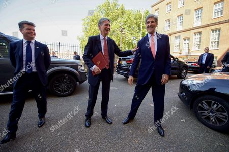 U.S. Secretary of State John Kerry, joined by U.S. Ambassador to the United Kingdom Matthew Barzun, bids farewell to his former counterpart, Philip Hammond, the ex-British Foreign Secretary and now Chancellor of the Exchequer, after they bumped into each other in Downing Street