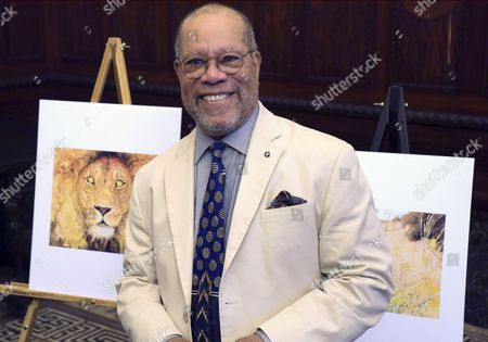 Stock Picture of Children's book illustrator Jerry Pinkney poses in front of two of his illustrations, at City Hall in Philadelphia. As Pinkney was honored by Philadelphia city officials Tuesday,  he said his hometown of Philadelphia and African-American history play powerful roles in his career illustrating more than 100 children's books.