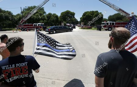 Lieutenant Nate Hatten with the Wills Point Fire and Rescue stands with Tom Rasmussen, right, of Argyle, Texas, as the limousine carrying family and friends of Dallas police Sgt. Michael Smith arrives at Restland Funeral Home and Cemetery, Thursday, July 14, 2016, in Dallas. Officer Smith was one of five police officers killed during protest in Dallas last Thursday.