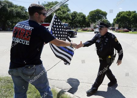 Stock Photo of Lieutenant Nate Hatten with the Wills Point Fire and Rescue shakes hands with a Dallas police officer who was greeting well wishers lining the street in front of Restland Funeral Home and Cemetery, Thursday, July 14, 2016, in Dallas. Dallas police Sgt. Michael Smith, who was buried at that location, was one of the five officers killed last Thursday during a protest.