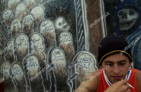 """"""" El Guero,"""" smokes a cigarette in front of a mural in memory of the deaths of fellow gang members, killed in fights with rival gang Mara 18 and in shootouts with police, in Guatemala City"""