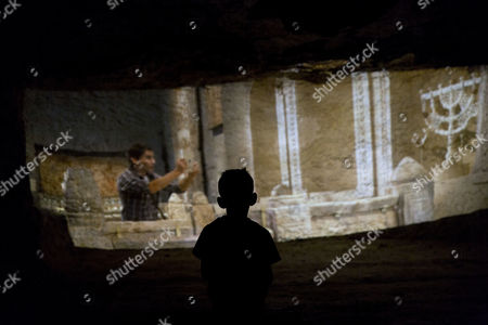A boy watches a short film about ancient Susiya, inside a cave where 34-year-old Palestinian Nasser Nawaja told Irish author Colm Toibin he was born, in the Susiya archaeological park, adjacent to the West Bank village of Susiya, south of Hebron.