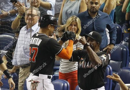 Miami Marlins' Giancarlo Stanton (27), is congratulated by hitting coach Barry Bonds after his two-run home run against the New York Mets during a baseball game in Miami, . At left is Marlins owner Jeffery Loria