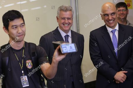 Brazil's Justice Minister Alexandre de Moraes, right, smiles next to Governor of Brasilia Rodrigo Rollemberg, center, as they watch a presentation by an agent of the Federal Police, during an inspection of safety procedures for the Rio 2016 Olympic Games, at the International Airport in Brasilia, Brazil
