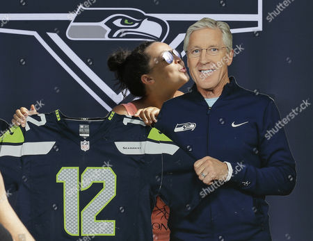 Ivy Lura, of Seattle, kisses a life-size figure of Seattle Seahawks head coach Pete Carroll as a friend takes her photo outside CenturyLink Field, , in Seattle. More than two thousand people were at the field Monday to buy single-game tickets for upcoming Seahawks home games