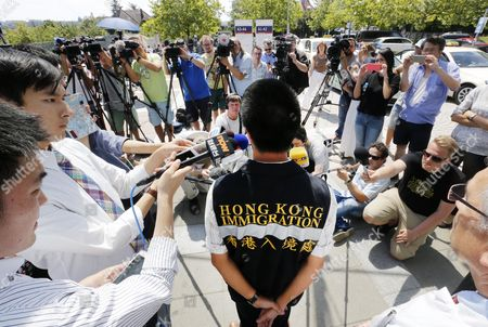 Kenneth Tong of the Hong Kong Immigration Center, center, talks to media people about the status of Hong Kong Citizen who were injured in an attack in front of the university hospital