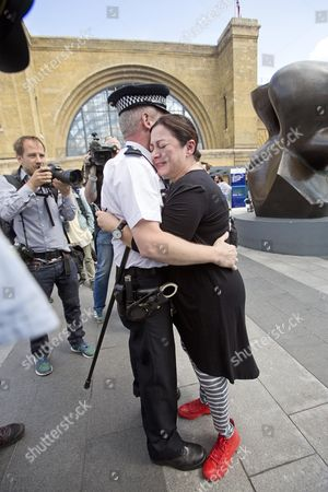 Walk Together For Peace - 7/7 London Bombings Survivor Gill Hicks Is Hugged By Pc Andy Maxwell (who May Have Rescued Her) At King's Cross. Faith Leaders From Muslim Jewish And Christian Faiths Walked With A Floral Tribute From King's Cross To Tavistock Square.