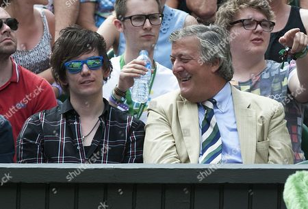 Stock Picture of Stephen Fry Watches The Tennis With His Partner Elliott Spencer. Day 8: Maria Sharapova V Coco Vandeweghe Wimbledon 2015 Tennis Championships Wimbledon London.