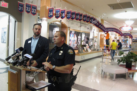 West Acres Mall property manager Chris Heaton, left, and Fargo Deputy Police Chief Joe Anderson talk in front of the Roger Maris Museum in Fargo, N.D., on , while workers repair a display where an ornate belt was stolen from the mall early Tuesday.