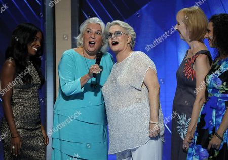 """Actresses Tyne Daly, center left, and Sharon Gless, center right, sing """"What the World Needs Now,"""" during the third day of the Democratic National Convention in Philadelphia , . Daly and Gless starred in the 80's police drama """"Cagney & Lacey"""