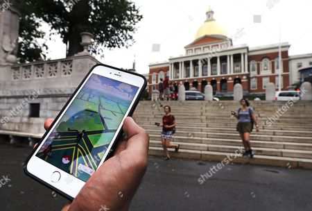 """Stock Image of A """"Pokemon Go"""" player shows his mobile phone while walking through the Boston Common, outside the Massachusetts Statehouse in Boston. Historical markers dot the landscape of old cities, barely noticed by passers-by. The founder of the volunteer-based historical markers website that licensed its data to game-maker Niantic Labs five years ago said he hopes enough people take their eyes off the Pokemon they're trying to catch to read the history on the markers. On the opposite side of the wall, left, is a bronze memorial to Robert Gould Shaw and the 54th Regiment Massachusetts Volunteer Infantry, comprised of black Union soldiers who fought in the Civil War"""