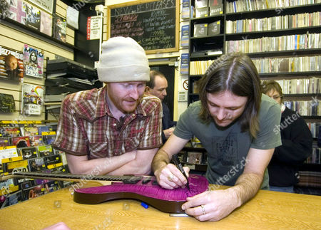 THE STORYS LEAD SINGER STEVE BALSAMO DRAWS A SHEEP ON A FAN'S GUITAR AS DAI SMITH LOOKS ON. THEY PLAYED AN ACOUSTIC GIG INSIDE THE STORE TO RELAUNCH THEIR DEBUT ALBUM AFTER BEING SELECTED TO SUPPORT ELTON JOHN ON HIS NEXT TOUR OF THE UK