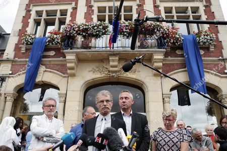 Saint-Etienne-du-Rouvray Mayor Hubert Wulfranc, center left, delivers his speech to the media in front of city hall a day after an hostage taking left a priest dead in Saint-Etienne-du-Rouvray, Normandy, France