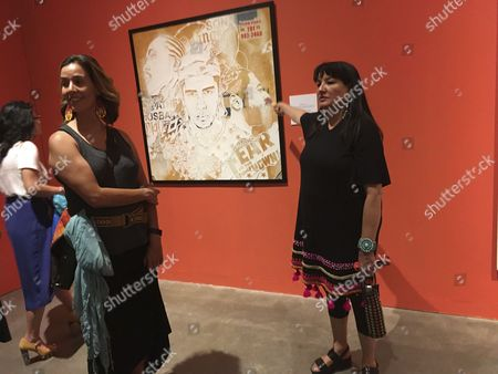 """Mexican-American author Sandra Cisneros, right, points to a piece of art next to poet Michelle Otero, left, at the National Hispanic Cultural Center in Albuquerque, N.M. at an exhibit based by Cisernos' 1984 novel """"The House of Mango Street."""" The exhibit """"The House on Mango Street: Artists Interpret Community"""" features major themes of the novel of a Mexican-American girl coming of age in Chicago"""