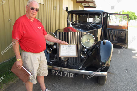 Tom Kenville, a member of the board of directors of the Bonanzaville museum in West Fargo, North Dakota, holds up a certificate for a 1936 Rolls-Royce automobile that was owned by Edward Stanley, son of the man who founded the Stanley Cup.