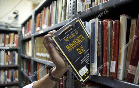 Stock Image of A librarian of the Sahitya Akademi Library shows a book written by Mahasweta Devi, in New Delhi, India