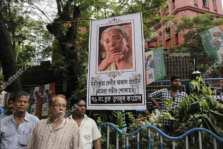 """People follow the funeral of Indian writer and social activist Mahasweta Devi in Kolkata, . Writing mostly in the Bengali language, Devi's major works dealt with the suffering of poor laborers and forest dwellers who had lost their lands due to industrial and urban growth. She founded several social organizations to help fight for the rights of indigenous people. The banner with a picture of Devi reads in Bengali """"We are deeply sorrowful due to the sudden demise of devi"""