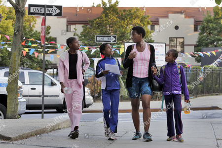 Tonia Handy, 46, is surrounded by her children, Tai Sheppard, 11, Rainn Sheppard, 10, and Brooke Sheppard, 8, left to right, walk home after track workouts at Boys and Girls High School, in the Brooklyn borough of New York.
