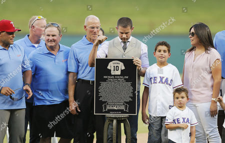 Former Texas Ranger Michael Young celebrates being inducted into the team's Hall of Fame, before the Rangers' baseball game against the Kansas City Royals on , in Arlington, Texas