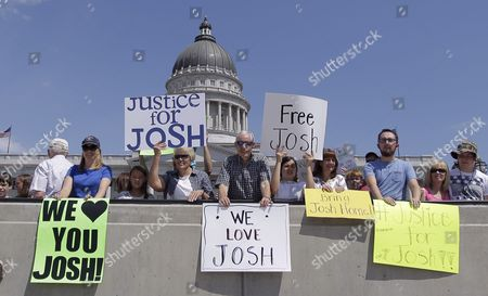People hold signs during a rally for Josh Holt, an American jailed in Venezuela, at the Utah State Capitol, in Salt Lake City.