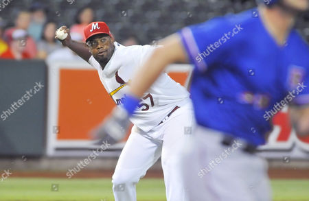 Memphis pitcher Jerome Williams (left) looks to throw towards first base after recovering a ground ball during the fifth inning of a MiLB baseball game between the Round Rock Express and Memphis Redbirds at AutoZone Park in Memphis, Tennessee