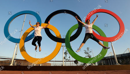Emily Bevan, left, and Victoria Fecci, pose for a photo with the Olympic Rings at the Olympic Park in Rio de Janeiro, Brazil