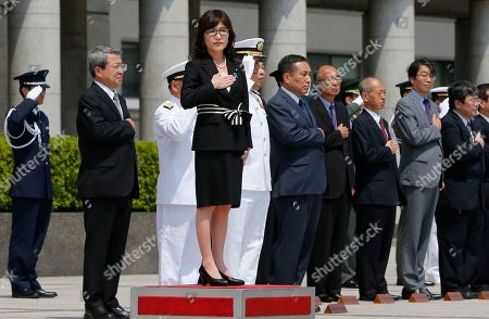 Japan's new Defense Minister Tomomi Inada salutes before inspecting an honor guard on her first day at Defense Ministry in Tokyo, . Inada, a former reform minister who most recently was policy chief in the ruling Liberal Democratic Party, replaced Gen Nakatani as defense minister. She is the second female to fill the post