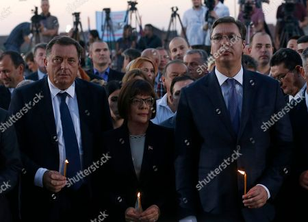 """Serbian Prime Minister Aleksandar Vucic, right, Milorad Dodik President of the Republika of Srpska entity of Bosnia and Herzegovina, left, and Serbian Parliament President Maja Gojkovic hold candles during a memorial service for the victims of the Croatian """"Storm"""" offensive, to mark the 21th anniversary in the village of Busije, some 25 kilometers (15 miles) west of Belgrade, Serbia"""