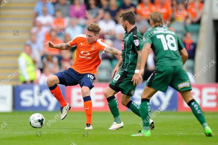 Stock Photo of Luton Town defender Glen Rea (16)  and Plymouth Argyle midfielder Graham Carey (10) during the EFL Sky Bet League 2 match between Plymouth Argyle and Luton Town at Home Park, Plymouth