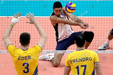 Stock Image of Eder Carbonera, Evandro M. Guerra, Taylor Sander United States' Taylor Sander bumps as Brazil's Eder Carbonera, left, and Evandro M. Guerra, right, watch during a men's preliminary volleyball match at the 2016 Summer Olympics in Rio de Janeiro, Brazil