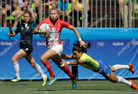 Great Britain's Emily Scott, left, avoids a tackle from Brazil's Isadora Cerullo, on her way to score a try