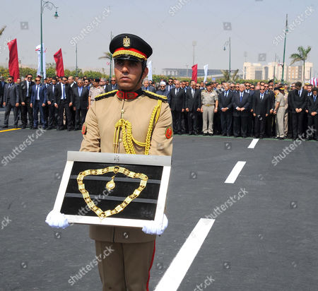 An officer carries the Order of the Grand Collar of the Nile, Egypt's highest state honour which was awarded to Egyptian-American Ahmed Zewail
