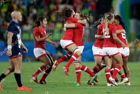 Canada's players celebrate as Great Britain's Heather Fisher, left, walks past during the women's rugby sevens bronze medal at the Summer Olympics in Rio de Janeiro, Brazil