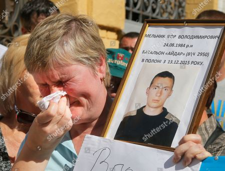 """A mother of a Ukrainian prisoner of war wipes her tears as she holds up her son's portrait, at a rally near the President's Office in Kiev, Ukraine,. Writing on the portrait reads: """"Igor Melnik, prisoner of war since December 2015."""" The rally was organized by lawmaker and former prisoner of war Nadezhda Savchenko to urge the authorities to speed up release of the Ukrainian prisoners of war from Russian jails"""
