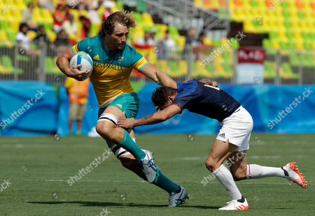Australia's Jesse Parahi, left, avoids a tackle by France's Terry Bouhraoua, during the men's rugby sevens match at the Summer Olympics in Rio de Janeiro, Brazil