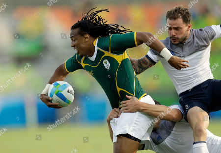 South Africa's Cecil Afrika, left, breaks away from France's Terry Bouhraoua, during the men's rugby sevens match at the Summer Olympics in Rio de Janeiro, Brazil