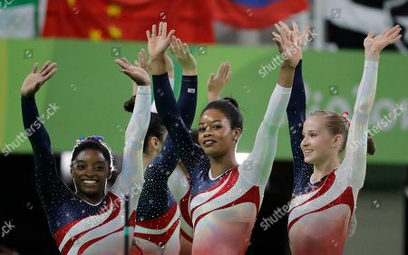 U.S. gymnasts, left to right, Simone Biles, Gabrielle Douglas and Madison Kocian wave to the audience at the end of the artistic gymnastics women's team final at the 2016 Summer Olympics in Rio de Janeiro, Brazil