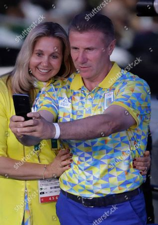 Former Ukrainian pole vaulter and IOC vice president Sergei Bubka, right, and his wife Liliana Bubka take a selfie during the opening ceremony for the 2016 Summer Olympics in Rio de Janeiro, Brazil