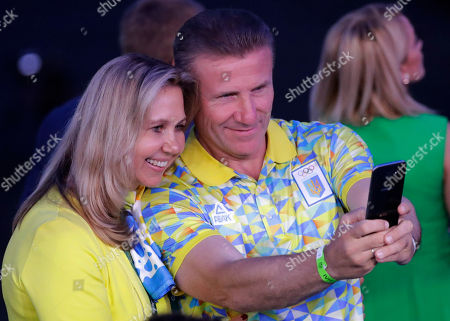 Former Ukrainian pole vaulter and IOC Vice President Sergei Bubka, right, takes a selfie with his wife Liliana Bubka prior to the opening ceremony for the 2016 Summer Olympics in Rio de Janeiro, Brazil