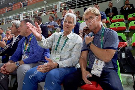 Olympic gold medal swimmer Mark Spitz speaks with Olympic gymnast Bart Conner during a preliminary round of men's gymnastics at Olympic Park