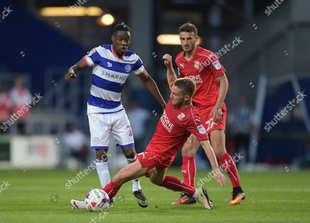 Anton Rodgers of Swindon Town tackles Olamide Shodipo during the EFL Cup First Round match between QPR and Swindon Town played at Loftus Road, London on 10th August 2016