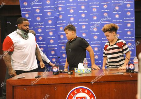 Texas Rangers designated hitter Prince Fielder #84 announces at the age of 32 in a press conference that his doctor will not medically clear him to return to the game of baseball after having his second neck surgery in 27 months as Fielders agent Scott Boris and Fielders sons Haven and Jaden (far right before an MLB game between the Colorado Rockies and the Texas Rangers at Globe Life Park in Arlington, TX Albert Pena/CSM