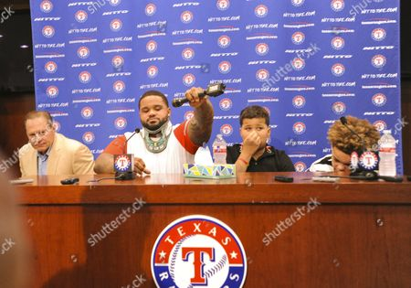 Texas Rangers designated hitter Prince Fielder #84 drops the mic after he announces at the age of 32 in a press conference that his doctor will not medically clear him to return to the game of baseball after having his second neck surgery in 27 months as Fielders agent Scott Boris and Fielders sons Haven and Jaden (far right before an MLB game between the Colorado Rockies and the Texas Rangers at Globe Life Park in Arlington, TX Albert Pena/CSM
