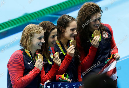 The United States team, Allison Schmitt, Leah Smith, Maya Dirado and Katie Ledecky, from right, hold up their gold medals after winning the women's 4x200-meter freestyle relay during the swimming competitions at the 2016 Summer Olympics, in Rio de Janeiro, Brazil