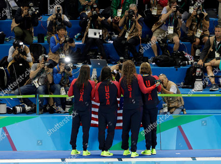 The United States team, Allison Schmitt, Leah Smith, Maya Dirado and Katie Ledecky, hold up their gold medals for the media after winning the women's 4x200-meter freestyle relay during the swimming competitions at the 2016 Summer Olympics, in Rio de Janeiro, Brazil
