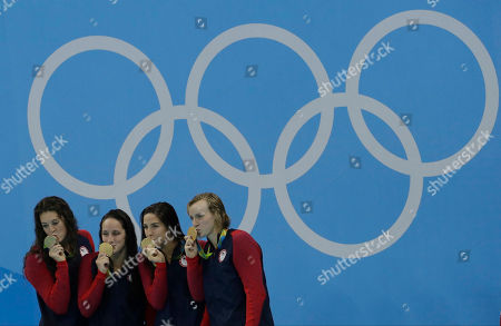 United States' Allison Schmitt, Leah Smith, Maya Dirado and Katie Ledecky, from left, kiss their gold medals after winning the women's 4x200-meter freestyle relay during the swimming competitions at the 2016 Summer Olympics, in Rio de Janeiro, Brazil