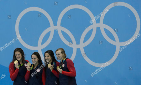 United States' Allison Schmitt, Leah Smith, Maya Dirado and Katie Ledecky, from left, hold up their gold medals after winning the women's 4x200-meter freestyle relay during the swimming competitions at the 2016 Summer Olympics, in Rio de Janeiro, Brazil