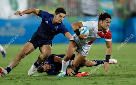 Japan's Teruya Goto, right, avoids a tackle from France's Terry Bouhraoua, bottom, and teammate Steeve Barry, during the men's rugby sevens match at the Summer Olympics in Rio de Janeiro, Brazil